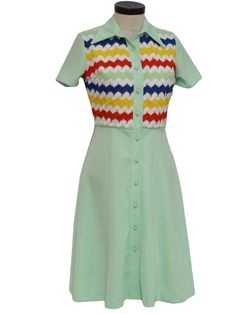 Polyecstatic!    70s -Care Label- Womens light sea foam green, white, yellow, red and blue banded geometric print mid length, short sleeve button front double knit polyester dress with fold over collar, empire waistline and a-line full skirt. Dress is vintage dead stock and has a light musty smell from years in storage, will go away after first wash.