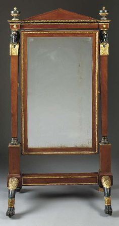 AN ITALIAN NEOCLASSIC ORMOLU-MOUNTED GILTWOOD, EBONIZED AND MAHOGANY CHEVAL MIRROR  First half 19th century, some surface decoration later   With a pedimented cresting above egg-and-dart molding over a rectangular glass swiveling between two Egyptian female caryatid supports, on pedestal bases on arched foliate carved paw legs