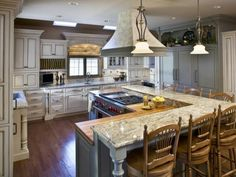 Ignore the faux-baroque styling.  This L-shaped kitchen island with raised bar is for serious kitchen entertaining; note the awesome gas range & hood.  Bring ALL your foodies!