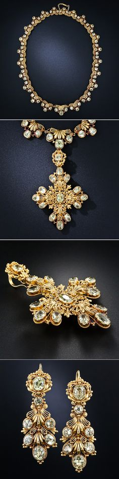 Transform yourself into a very fine lady from the early 19th century with this exquisite jewelry parure. This elegant antique suite provides all your jewelry needs with a necklace, earrings that can be worn two different ways, long or short, and a brooch that can also be used as a pendant dropped from the necklace. All the pieces nestle neatly into a velvet-lined fitted box. The lacy and delicately crafted jewels are all set with pale greenish-yellow chrysoberyls, which were popular at the…