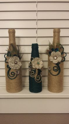 Set of 3 jute twine wrapped wine bottles. Beautiful modern decoration touch on them. Fabric flowers. Peacock feathers. Perfect for home