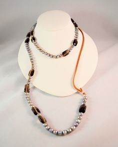 """-6mm freshwater pearls and 14x10mm Faceted Smokey Quartz Squares  -925 Sterling Silver, Leather, 100% Silk  -Length 43 inches + 2 inch extender  -6"""" Deer Hide Leather    A luxurious one of a kind macrame necklace that is dressy enough to wear for dressy holiday parties but still casual enough to wear everyday. Iridescent lavender freshwater pearls make up the majority of this necklace and are accented by glittering smokey quartz squares along it's length. Each of the beads are hand knotted…"""