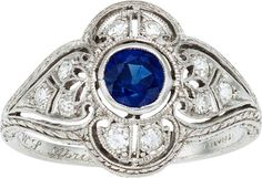 Art Deco Sapphire, Diamond, Platinum Ring, Tiffany & Co.  The ring features a European-cut sapphire weighing approximately 0.40 carat, enhanced by European-cut diamonds weighing a total of approximately 0.25 carat, set in platinum, marked Tiffany.