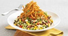 BJ's Copycat Barbecue Chicken Chopped Salad- Romaine and iceberg lettuce, corn, black beans, jicama, cilantro, mozzarella cheese, tomatoes and green onions. Tossed with BBQ ranch dressing and topped with crispy onion strings.