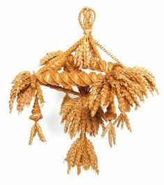 This corn dolly is 'Pembroke chandelier'. It was made by Alec Coker, an experienced corn dolly maker, to a design by Doreen Walmsley of Pembrokeshire. It consists of a spirally woven square structure as a base, with bunches of corn ears at each corner. Four plaited bands from the central hanging structure, holding two bunches of corn ears and with a lantern hanging from each corner.  (MERL/86/125)