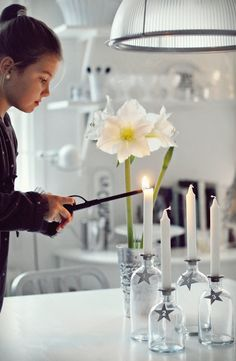 Simple candles in star decorated apothecary bottles: cut out the stars from silver cardboard and hang them with a string/ribbon around the bottle neck. If clear apothecary bottles are not available, use what you have.