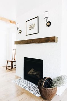 Credit: Jaclyn Paige white brick fireplace, wood beam hearth, blue and white tile around fireplace, wood floors Dining Room Fireplace, Fireplace Mantle, Fireplace Design, Simple Fireplace, White Brick Fireplaces, Subway Tile Fireplace, Tile Around Fireplace, Stucco Fireplace, Brick Hearth