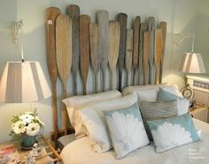 Vintage oars create a unique headboard that is perfect for a beach or lake house bedroom. Love it!