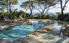 Piscine paysagée réalisée à partir d'une piscine traditionnelle existante. Création d'un univers rocheux qui s'intègre à l'environnement de bord de mer.
