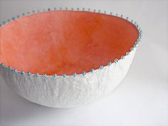 Cast paper bowl with coral-colored tissue paper lining, white exterior and beads embedded in the rim, made from recycled paper