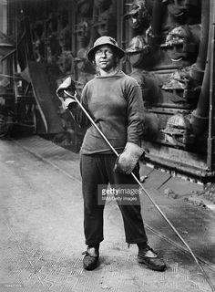 Women's War Work During The First World War, London, 1918, A full-length portrait of a female retort house worker, her face blackened with grime, as she stands in front of the furnaces at the South Metropolitan Gas Company, Old Kent Road, London. She is wearing trousers, jersey, cap and heavy duty gloves, and is holding a rake, June 1918.