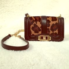 """Rebecca Minkoff Mini Leopard Crossbody Such a STUNNING leopard crossbody by Rebecca Minkoff. The front had a leopard pattern fabric mixed with black leather. The front also has a beautiful gold closure. The back has a pocket & in all black leather with the Rebecca Minkoff gold plate. The dimensions are 7"""" W, 4 1/2 L, 2 1/2 D. The inside is lined in a silk leopard print fabric and has an inside fabric. The strap is 21 1/2"""" and is part gold chain & leather. New, never worn, with original tag…"""