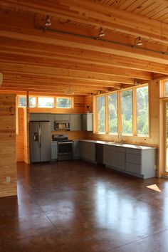 View of cabin interior showing kitchen and dining area - no furniture yet. Modern mountain farmhouse, cabin, corten steel metal roofing, cedar siding, pine paneling interior, marvin windows and doors, casement windows, glulam beams, tongue and groove floor decking, tongue and groove roof deck, SIPs panels, stained concrete floor, open floor plan, loft, alternating tread stair, architectural design, architect, mountain views, front porch, venacular design Stained Concrete, Concrete Floors, Casement Windows, Windows And Doors, Design Architect, Architecture Design, Steel Metal, Metal Roof, Dining Area