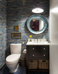 Colorful wallpaper in dim-lit bathroom with round mirror, dark cabinetry, and marble sink