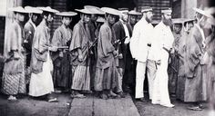 A group of samurai wearing jingasa and walking with westerners..