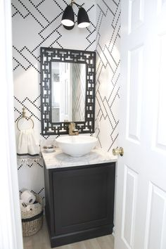 black and white powder room with sharpie stenciled walls, custom vanity light, marble counters, vessel sink, brass faucet and vintage touches