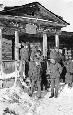German soldiers pose outside of a commandeered house used as a billet in an occupied Russian village.