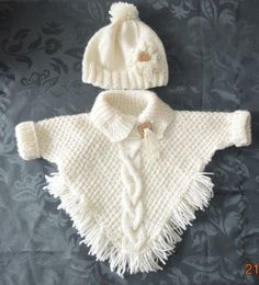 Cute poncho with sleeves and hatThe poncho is knitted in barley grainIn the middle of a wired cableThe hat has a crocheted flowerHave used 2 different thicknesses of wool here