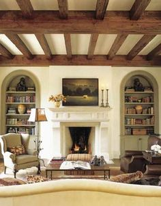 love the exposed wood beams, fireplace, and bookcases