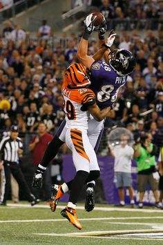 Tight end Dennis Pitta #88 of the Baltimore Ravens catches a touchdown pass in front of cornerback Leon Hall #29 of the Cincinnati Bengals during the second half at M Bank Stadium on September 10, 2012 in Baltimore, Maryland.