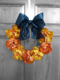 Rich autumn/fall colored peonies in orange and yellow/orange, adorned with a glittering, wide, wired black bow!   Also an elegant Halloween decoration for your door or party!