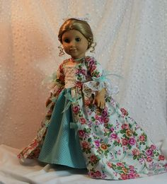 $55.00 TheWhitePoodle - This listing includes a gorgeous colonial ball gown with attached aqua diamond print petticoat, white pinner cap with aqua sheer ribbon, square swiss dot fichu, and pearl choker with a carved resin rose for 18 inch dolls Felicity and Elizabeth or any other 18 in doll that feels like