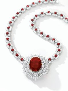 Rubellite, Ruby and Diamond Necklace Set with an oval rubellite weighing 42.09 carats, to a stylised surround set with variously-shaped diamonds, the necklace composed of links set with oval rubies and baguette diamonds, connected by brilliant-cut diamonds, the rubies and diamonds together weighing approximately 12.85 and 21.30 carats respectively, mounted in 18 karat white gold, length approximately 430mm, signed Laut and numbered 7389.