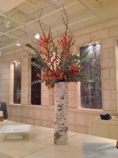 fall birch buffet arrangement for a design showroom with eucalyptus, orange ilex berries and rain tree foliage.