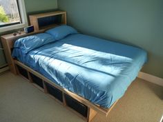 Double bed with storage containers underneath.Headboard for books etc.  Designed, created and made by Chris Ellsay.