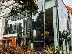 Foto do espelhamento do skyline da cidade de São Paulo através de uma agência do ITAU