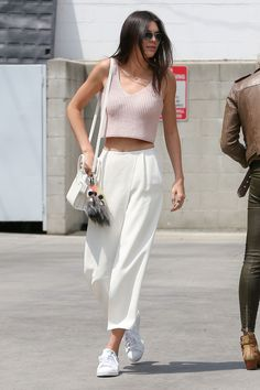 The model keeps it casual in a light pink crop top and frothy white pants.   - MarieClaire.com