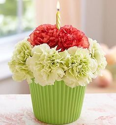 Flower Cupcake  This cute cupcake is the perfect addition to any celebration.  Bright coloured carnations are arranged in a ceramic cupcake holder.  A birthday candle tops off the design.    Colours may vary with availability, but you can request a colour choice under special requests.  Toronto Flowers by 4165flower.com