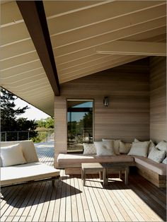 Shelter Island Covered patio with bench set and throw pillows Muted colors wood tones