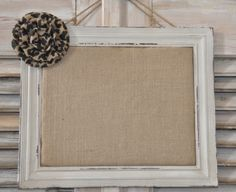 Creme colored distressed frame with padded burlap backing.  Embellished with burlap flower.  Can be hung horizontally or vertically.  Push pins included to display up to an 8x10 photo or use as a bulletin board for miscellaneous items.  The possibilities are endless with this frame!