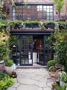 Flowers tumbling from flower boxes, vibrant green ground covers and neatly trimmed hedges combine beautifully with these large abstractly shaped cement tiles and square metal-framed windows and doors. All elements combine for a beautiful backyard in this Manhattan home.