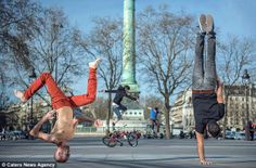 Upside down: Kapstand is joined by other dancers on the streets of Paris