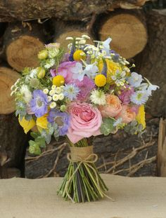Colourful Summer Bridal bouquet made using Garden Roses, Scabious, Delphiniums, Nigella, Craspedia, Tanacetum & Eucalyptus
