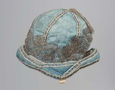 Child's cap, 18th century. Pale blue silk damask trimmed with metallic lace.