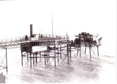 In around 1900, passengers board Volk's 'Daddy Long Legs', sea-going car, which is about to make the three-mile journey on its stilts to the Banjo Groyne in Kemp Town, Brighton. The steel pier was about 100 yards long.
