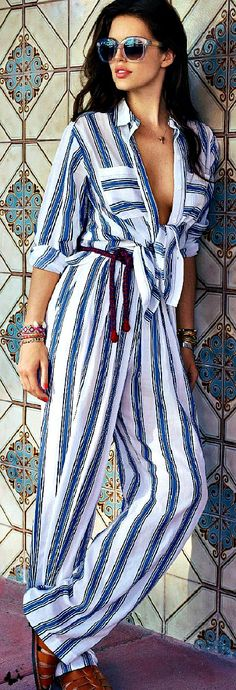 Deep décolletage snowy jumpsuit w/ blue stripes & red wine waistcord, chestlength raven hair, mauve lips, clear-framed black-lensed shades; turquoise/brown/cream tile wall