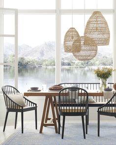 A wood dining table surrounded by black modern dining chairs and rattan pendants completes this dining room inside a waterfront home. Black Dining Chairs, Table And Chairs, Rattan Dining Chairs, Modern Dining Room Chairs, Neutral Dining Rooms, Coastal Dining Rooms, Next Dining Chairs, Modern Dining Room Lighting, Farmhouse Dining Chairs