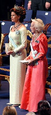 Queen Silvia at the 2004 Nobel Prize Award Ceremony standing beside Princess Lillian in an orange creation.