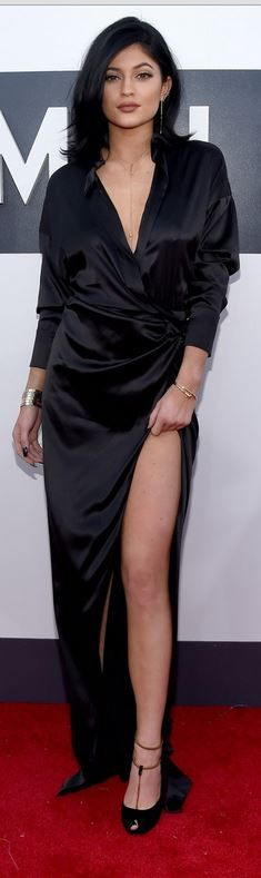 Who made Kylie Jenner's black wrap dress, gold jewelry, and suede chain pumps