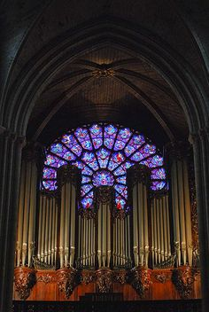 Huge Pipe Organ and a stained glass window of Notre-Dame, Paris,France. The size of the pipes for the organ are truly massive!