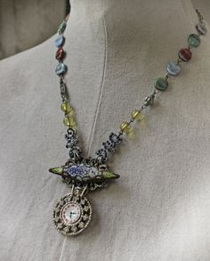 An unusual replica of a time piece is the pendant of this unique necklace. The face is mother of pearl and is surrounded with rhinestones. Hangs