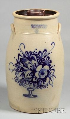 """Cobalt Decorated Six-Gallon Stoneware Churn with Cover, """"J. & E. NORTON, BENNINGTON VT.,"""" 1850-61, elongated oval churn with applied lug handles, incised line about the shoulder, decorated with a cobalt blue glazed bouquet of flowers in a footed bowl, Albany slip-glazed interior and cover,"""