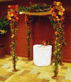 Beautiful #wedding structure adorned with #twigs and fall colored flowers to make this indoor wedding ceremony stand out.
