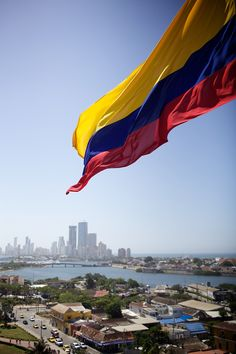 A giant Colombian flag waves atop El Castillo de San Felipe with both modern and colonial Cartagena in the distance.