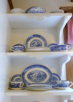 Open shelving against white bead board in my farm house kitchen display my grandma's blue willow dishes.