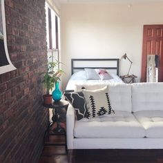 Pin for Later: How to Style Your Bed in a Small Space Cornered by the Couch This studio creates separate living and bedroom spaces by using the couch as a natural room divider.